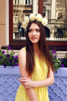 Adatti il ritratto della ragazza castana graziosa giocosa felice che sorride e che si diverte, indossando il vestito giallo pastello e la corona delle rose.