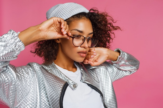 Fashion portrait of  mix race woman with brown skin and curly african hairstyle on vivid pink background. wearing silver winter  jacket and grey hat.