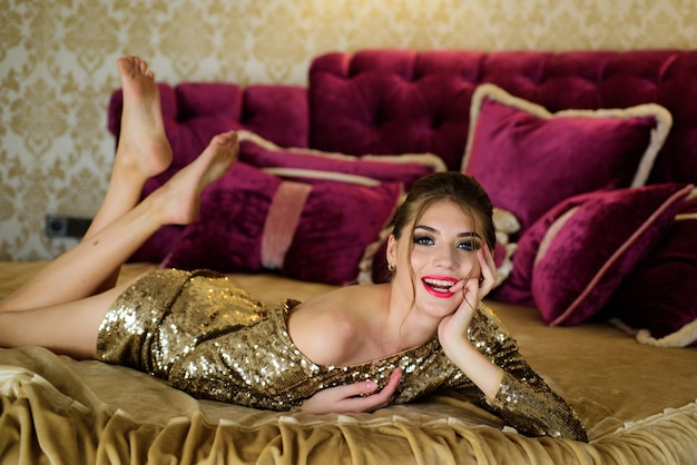 Fashion portrait of model indoors luxurious bedspread and cushions romantic beautiful woman lying in...