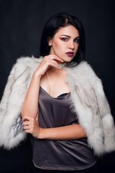 豪華なアクセサリーが付いている毛皮の美しいブルネットの少女のファッションの肖像画。黒い背景にジュエリーを持つ美容モデル。白いミンクの毛皮のコートの女の子。美しい豪華な冬の女性。