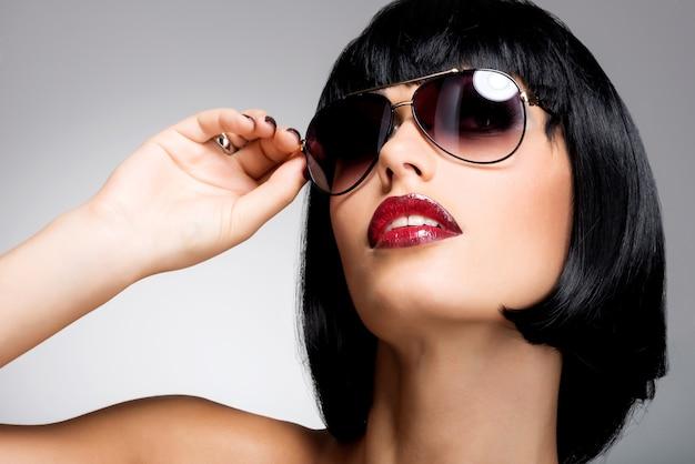 빨간 선글라스와 샷된 헤어 스타일을 가진 아름 다운 갈색 머리 여자의 패션 초상화