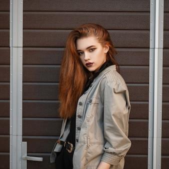 세련된 재킷과 거리의 게이트 근처에서 포즈를 취하는 검은 폴로 셔츠에 아름다운 유행 여자의 패션 초상화