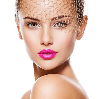 아름 다운 여자의 패션 초상화는 얼굴에 황금 베일을 착용합니다. 핑크 입술. 흰 벽에 절연