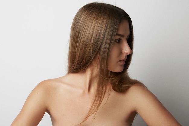 Фасонируйте портрет красивой улыбающейся женщины с длинными волосами на пустом светлом фоне. мода.