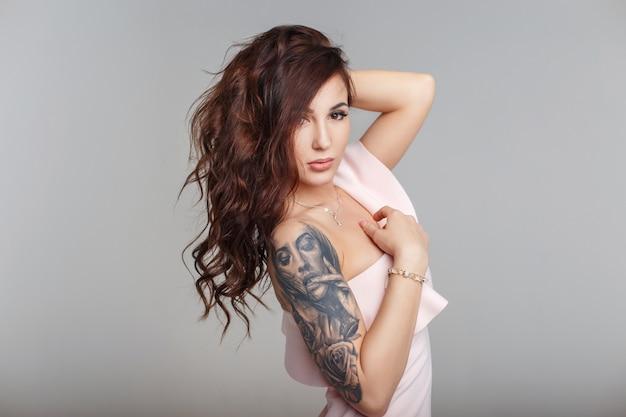 회색 배경에 세련된 핑크 드레스에 그녀의 팔에 문신과 머리를 가진 아름다운 젊은 여자의 패션 초상화