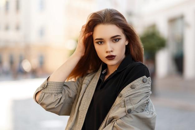 세련 된 재킷과 거리에서 포즈를 취하는 유행 셔츠에 메이크업으로 아름 다운 젊은 여자의 패션 초상화