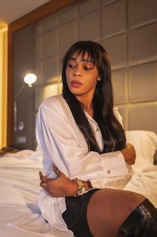 ホテルのベッドで黒人アフリカ民族の女の子のファッションの肖像画。彼女は白いシャツ、背の高いブーツ、黒いスカートを着ています。通りへの夜の予定の前に見つける