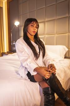 ホテルのベッドで黒人アフリカ民族の女の子のファッションの肖像画。彼女は白いシャツ、背の高いブーツ、黒いスカートを着ています。縦の写真