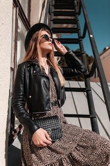 Фасонный портрет красивой молодой женщины в шляпе солнцезащитных очков в модной кожаной куртке и платье с сумочкой позирует на лестнице в городе