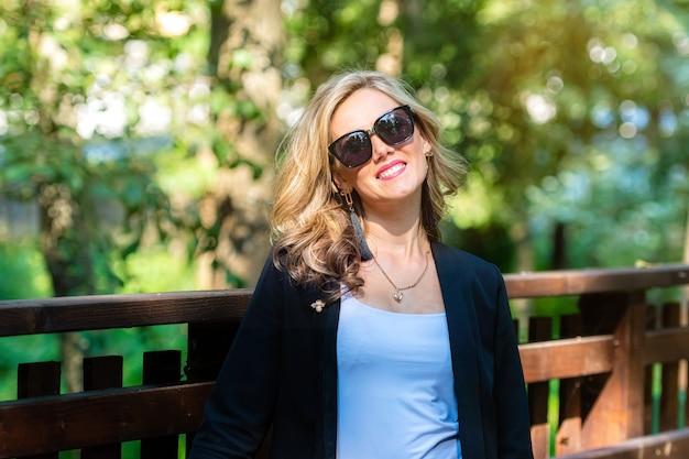 Модный портрет стильной красивой блондинки в солнцезащитных очках на фоне расфокусированного парка