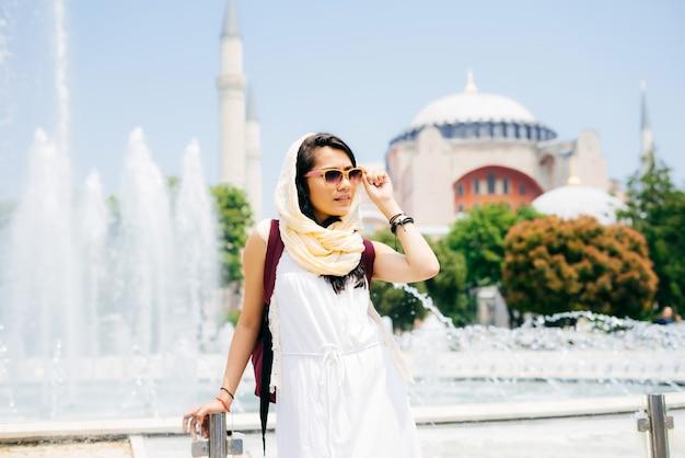 여름 방학에 젊은 현대 이슬람 여성의 패션 초상화는 안경을 쓰고, 멀리 보이는 모스크를 배경으로 합니다. 여름 여행, 휴가