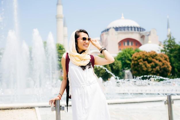 여름 방학에 안경을 쓰고 있는 젊은 현대 이슬람 여성의 패션 초상화는 배경에 있는 모스크인 먼 곳을 바라보고 있습니다. 여름 여행, 휴가
