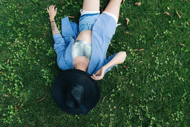 Фасонируйте портрет молодой женщины, одетой в синюю полосатую куртку и черную шляпу. женщина лежит на зеленой лужайке в парке
