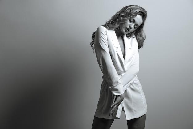 長い髪の驚くべき若い女性のファッションの肖像画は白いジャケットを着ています。モノクロカラー。テキスト用のスペース