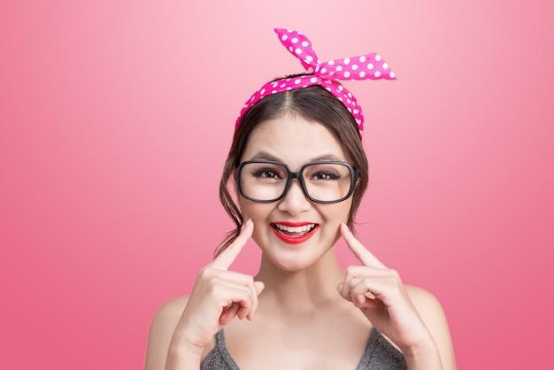 Фасонируйте портрет азиатской девушки с очками, стоящими на розовом фоне.