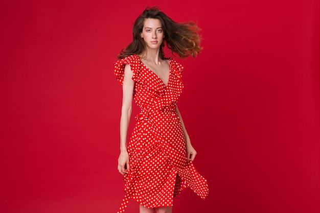 赤いスタジオに赤い点線のドレスで魅力的な笑顔の若い女性のファッションの肖像画