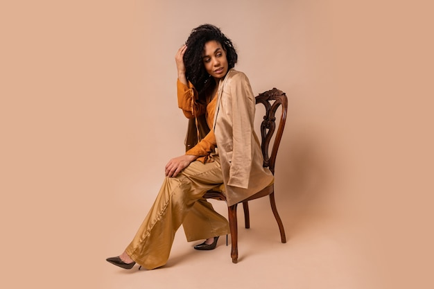 Фасонируйте портрет привлекательной женщины с загорелой кожей с идеальными вьющимися волосами в элегантной оранжевой блузке и шелковых брюках, сидящей на старинном стуле на бежевой стене.