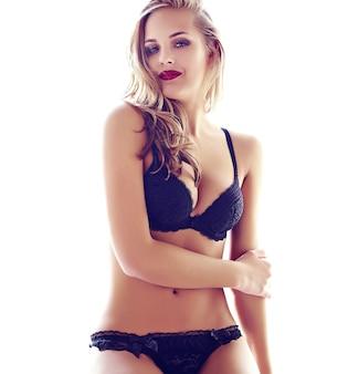 Фасонируйте портрет красивой сексуальной молодой модели взрослой белокурой женщины нося черное эротичное женское бельё представляя в светлом интерьере утром