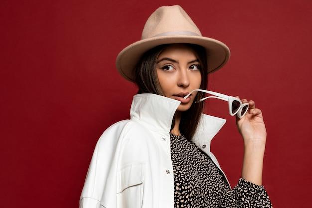 Фасонируйте портрет красивой стильной тощей женщины брюнет с одетым белым пальто и бежевой шляпой, держащей солнечные очки. осенний или зимний модный модный стиль.