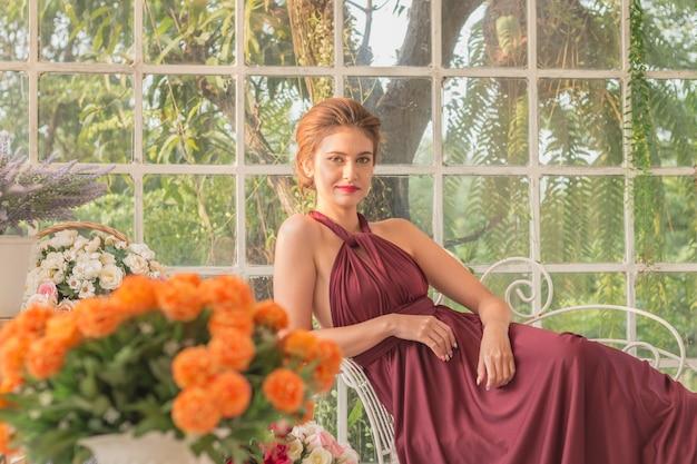 Мода портрет красивая женщина в саду стекла дом с платьем.