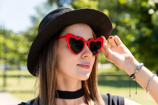 검은 티셔츠와 공원에서 산책하는 빨간 치마에 아름 다운 여자의 패션 초상화. 유행 의류 안경 액세서리. 쇼핑 판매 개념