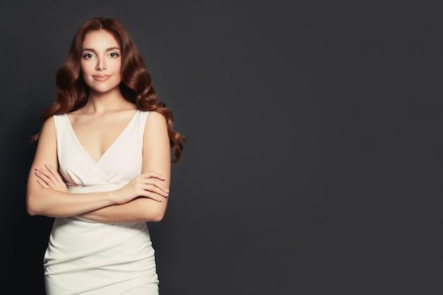 Фасонируйте портрет платья красивой женщины нося белого стоя против серого backgroung стены
