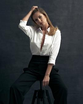 暗い背景のスタジオで白いシャツと黒のズボンと美しい女性のファッションの肖像画