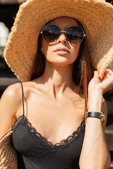トレンディな麦わら帽子とスタイリッシュな織りハンドバッグと黒のランジェリートップのヴィンテージラウンドサングラスと美しい若い女性のファッションの肖像画がビーチに立っています。女性の夏のスタイルの外観