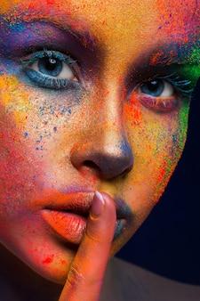 Портрет моды модели красоты с красочным порошком составляет знак тишины шоу. красивая женщина с творческим составом всплеска. абстрактное красочное искусство макияж, урожай
