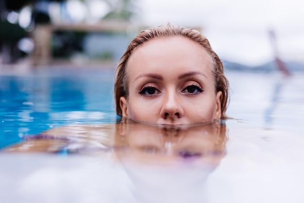 Модный портрет кавказской женщины в бикини в синем бассейне на отдыхе при дневном свете