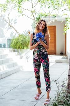 Модный портрет кавказской женщины в стильном летнем комбинезоне с цветами возле виллы