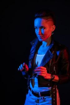 黒の背景に笑顔で創造的な照明と白人女性のファッションの肖像画