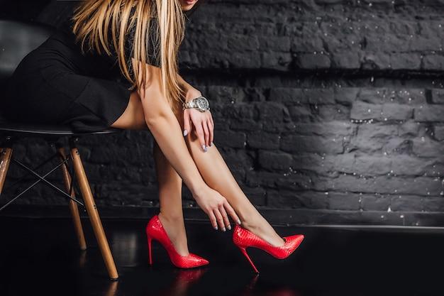 Фасонируйте портрет крупного плана, молодой элегантной женщины. черное короткое платье, сидя в кресле, изолированные студия выстрел, нога.