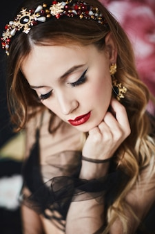 完璧なメイクと高価なトレンディなゴールドジュエリーを備えたエレガントで豪華な女性のファッションポートレート。ウェーブのかかった髪型、明るいメイク、セクシーな赤い唇を持つモデルの女の子。贅沢な生活。贅沢なファッション