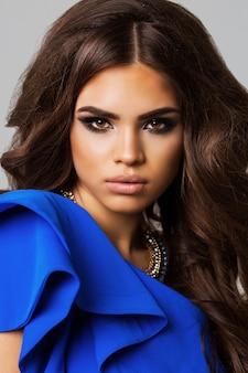 壮大な髪とエレガントな女性のファッションポートレート。ブルネットの少女。完璧なメイク