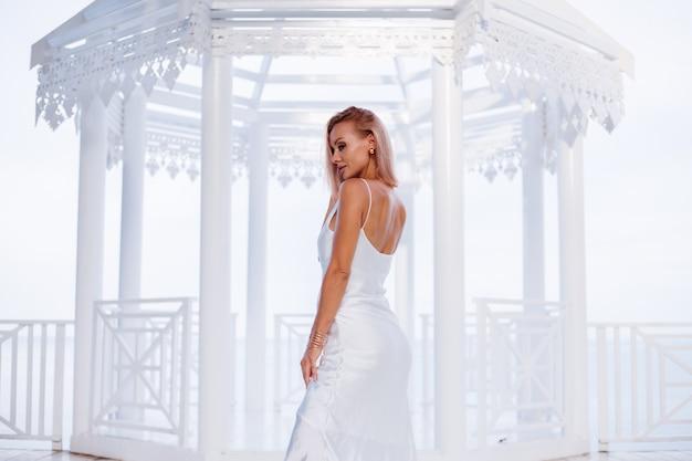 シルクホワイトの夏のロマンチックなドレスの黄金のブレスレットとイヤリングのヨーロッパのブロンドの女性のファッションの肖像画