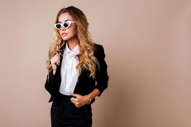 ベージュの壁でポーズスタイリッシュなカジュアルな黒のジャケットでゴージャスな金髪の女性のファッションの肖像画。白いレトロなメガネ。ハイファッションスタイル。