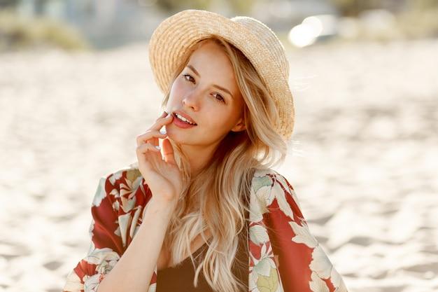 太陽が降り注ぐビーチで休んでいる自然なメイクでゴージャスな金髪の女性のファッションの肖像画。麦わら帽子をかぶっています。休日と休暇の気分。