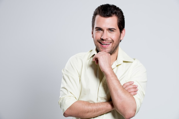 얼굴 포즈 근처 손으로 노란색 셔츠에 잘 생긴 행복 한 남자의 패션 초상화