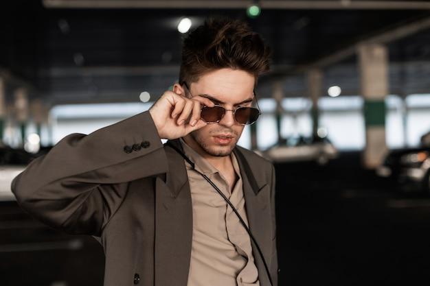 トレンディなブレザーとシャツを着たハンサムなヒップスターの男のファッションの肖像画は、街のサングラスを通して見えます。アーバン男性スタイル