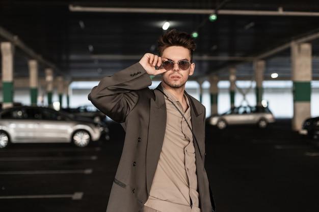街のサングラスを通して見ている男性のブレザーとシャツとトレンディな衣装でハンサムな若い男のファッションの肖像画
