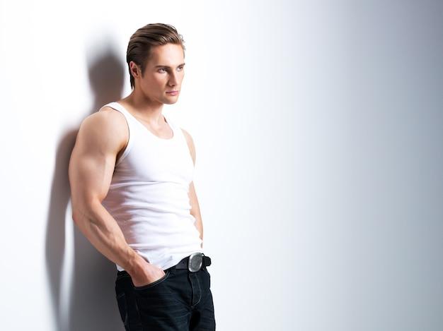 横向きの白いシャツを着たハンサムな若い男のファッションの肖像画は、コントラストの影で壁を越えてポーズします。