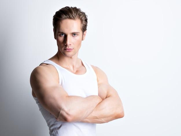 교차 팔 흰 셔츠에 잘 생긴 젊은 남자의 패션 초상화는 벽에 포즈.