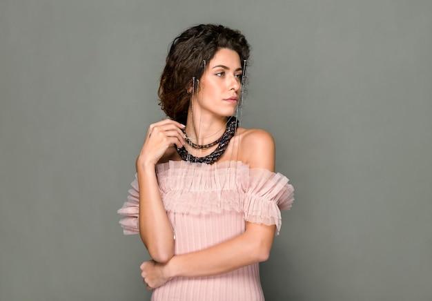Copyspace와 회색 스튜디오 배경 위에 측면을 찾고 크리스탈 액세서리를 입고 핑크 얇은 명주 그물 상단에 여자의 패션 초상화