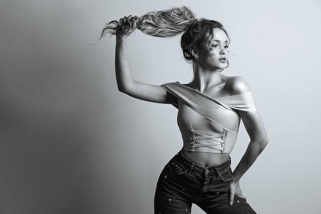 壮大な若い女性のファッションの肖像画は髪で自分自身を引っ張る。モノクロカラー。テキスト用のスペース