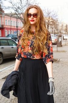 古いヨーロッパの都市の町の通りを一人で歩いて、レトロなエレガントな服とサングラスを着て楽しんで、かなりスタイリッシュな若い女性のファッションの肖像画。ヴィンテージの秋スタイル。