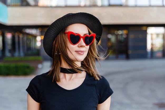 검은 t- 셔츠와 거리에 걷는 빨간 치마에 예쁜 여자의 패션 초상화. 유행 의류 안경 액세서리. 쇼핑 판매 개념