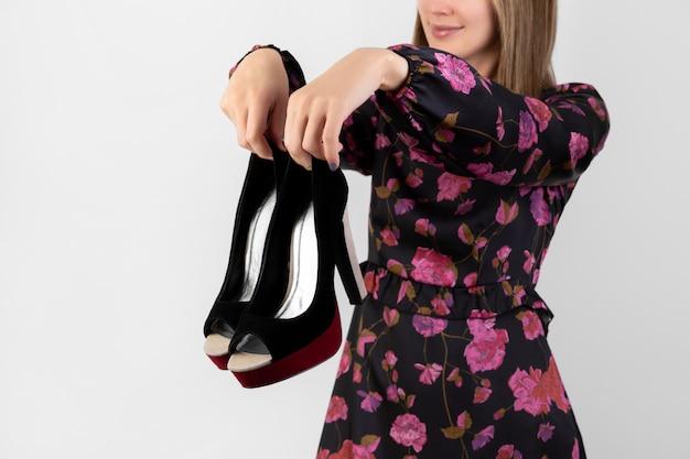 靴を保持している花柄のドレスのきれいな女性のファッションの肖像画。