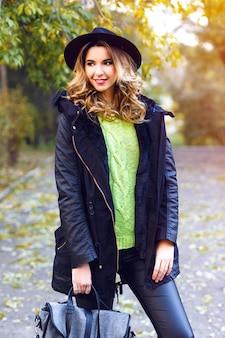 유행 코트, 빈티지 모자와 네온 스웨터를 입고 꽤 젊은 금발 웃는 여자의 패션 초상화, 좋은 화창한 가을 가을 날에 시골 공원에서 포즈.