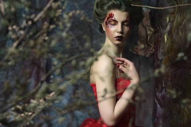 Фасонируйте портрет романтичной красивой девушки с прической, красными губами, художественным платьем. принцесса в таинственном доме. креативная концепция жили-были в фэнтези.